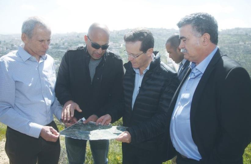 ZIONIST UNION head Isaac Herzog (second from right) and faction MKs Omer Bar-Lev (far left) and Amir Peretz (far right) stand on a Jerusalem hilltop yesterday for a briefing from Col. (res.) Shaul Arieli. (photo credit: MARC ISRAEL SELLEM/THE JERUSALEM POST)