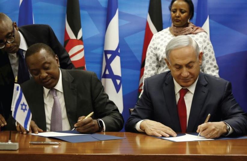 Kenya's President Uhuru Kenyatta and Prime Minister Benjamin Netanyahu sign agreements after they delivered joint statements in Jerusalem, February 23 (photo credit: REUTERS)