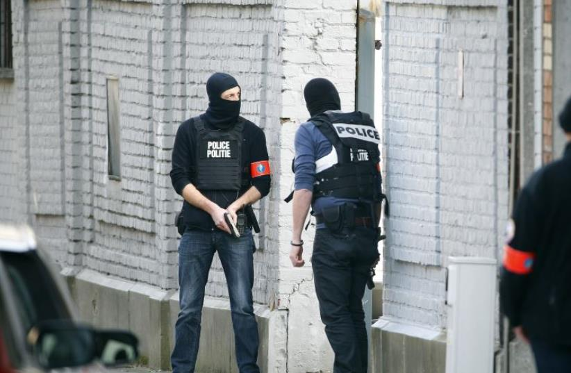 Police at the scene where shots were fired during a police search of a house in the suburb of Forest near Brussels, Belgium, March 15, 2016. (photo credit: REUTERS)