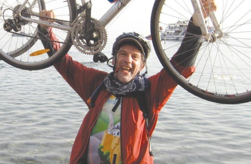FRANKLYN D. MEDJUCK holds up his bicycle in Eilat at the end of the Hazon Bike Ride marathon he did in Israel three years ago. (photo credit: Courtesy)