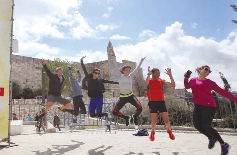 US ACTRESS Rachele Brooke Smith (third left) and friends get ready for the Jerusalem Marathon near Jaffa Gate yesterday. (photo credit: MARC ISRAEL SELLEM/THE JERUSALEM POST)