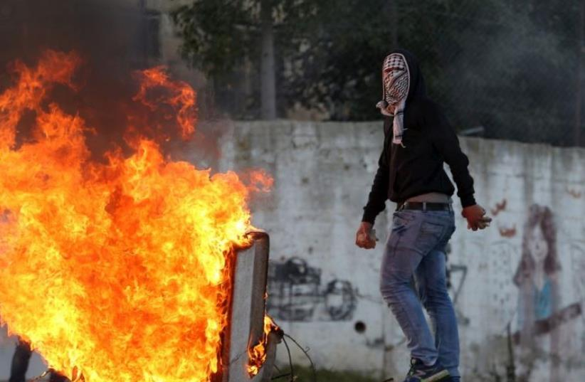 A Palestinian protester takes a position next to a fire during clashes with Israeli troops near Israel's Ofer Prison not far from Ramallah (photo credit: REUTERS)