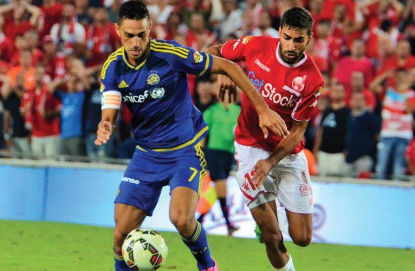 Maccabi Tel Aviv captain Eran Zahavi (left) and Hapoel Beersheba defender Ofir Davidzada are set to clash once more tonight when the Premier League's top two teams meet at Turner Stadium. (photo credit: MENI BEN-ARI)