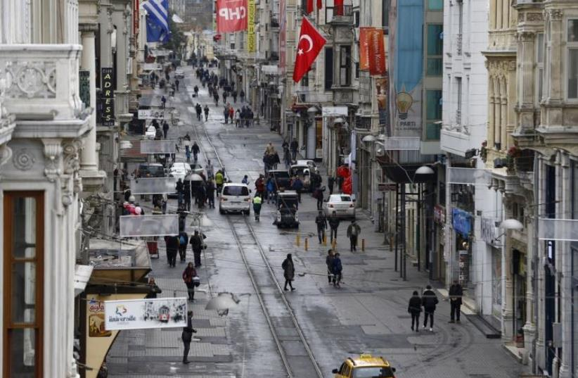 Pedestrians walk along Istiklal Street, a major shopping and tourist district, in central Istanbul (photo credit: REUTERS)