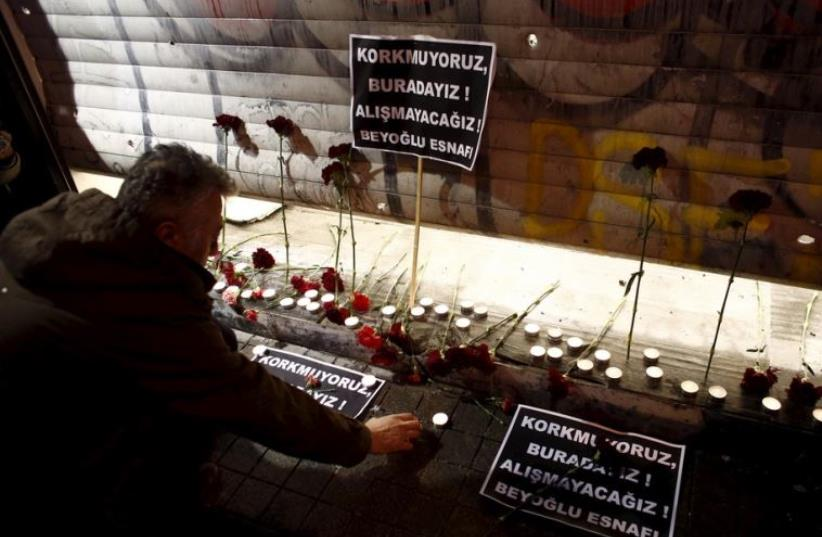 A man places carnations and a candle at the scene of a suicide bombing at Istiklal street, a major shopping and tourist district, in central Istanbul (photo credit: REUTERS)
