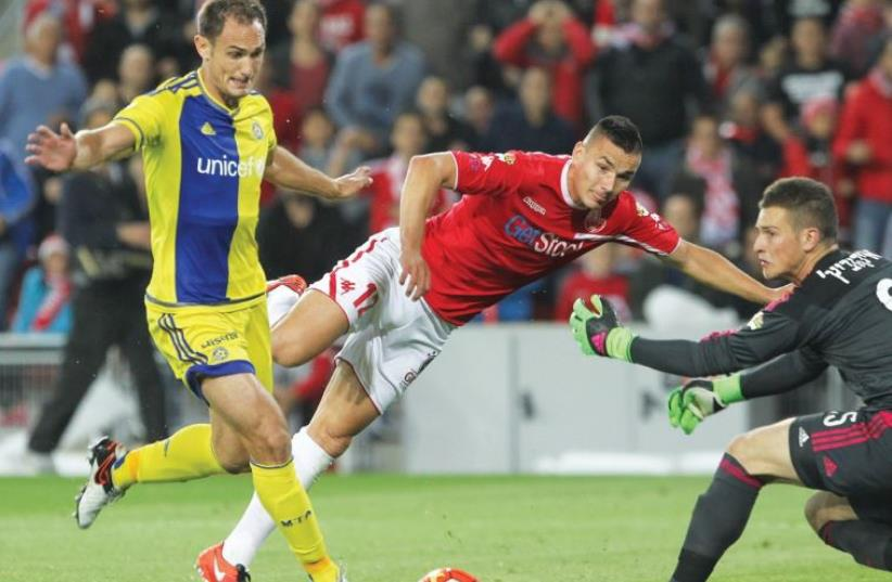 Hapoel Beersheba midfielder Ovidiu Hoban (center) scores past Maccabi Tel Aviv goalkeeper Predrag Rajkovic to cancel out Carlos Garcia's (left) opener for the yellow-and-blue in last night's 1-1 draw at Turner Stadium. (photo credit: DANNY MARON)