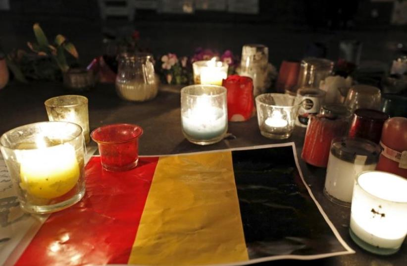 Candles are pictured around a Belgian flag on the Place de la Republique in Paris (photo credit: REUTERS)