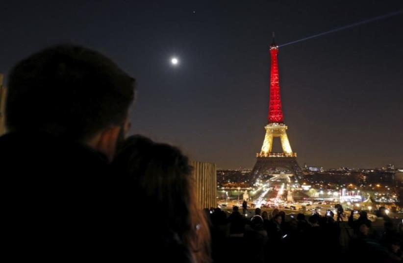A couple looks at the Eiffel Tower lit up in the colors of the Belgian flag in Paris (photo credit: REUTERS)