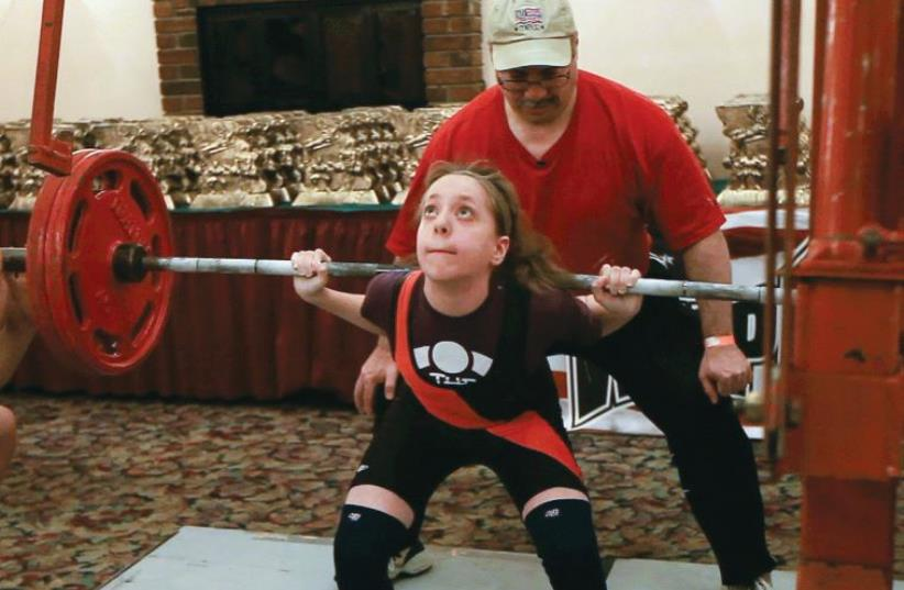At age 11, Kutin squatting 225 lbs to break the all-time world record in the 97 pound weightclass in 2013 (photo credit: Courtesy)
