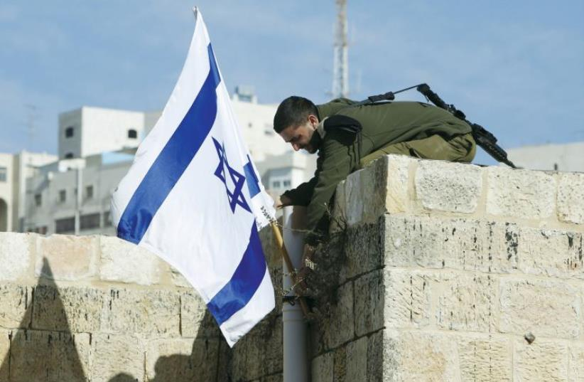 An Israeli solider removes the flag from a rooftop in Hebron as troops force Jewish settlers out of homes they said they had purchased from Palestinians (photo credit: REUTERS)