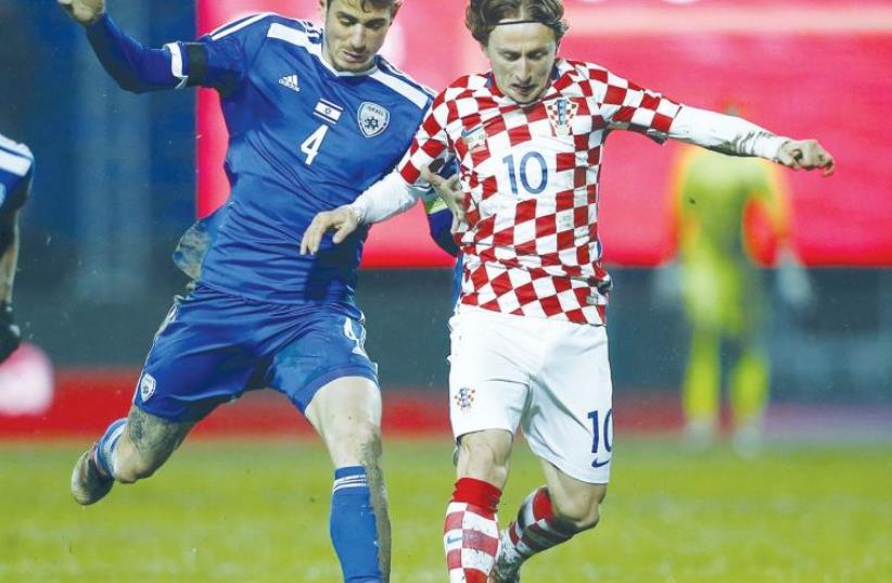 Israel midfielder Nir Biton (left) battles Croatia's Luka Modric for the ball during last night's 2-0 defeat in an international friendly in Osijek (photo credit: REUTERS)