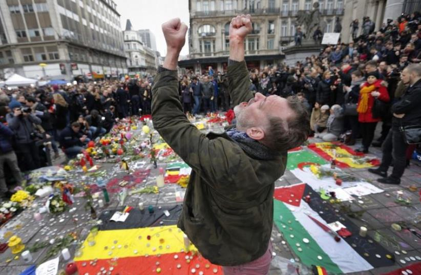 A man reacts at a street memorial following Tuesday's bomb attacks in Brussels (photo credit: REUTERS)