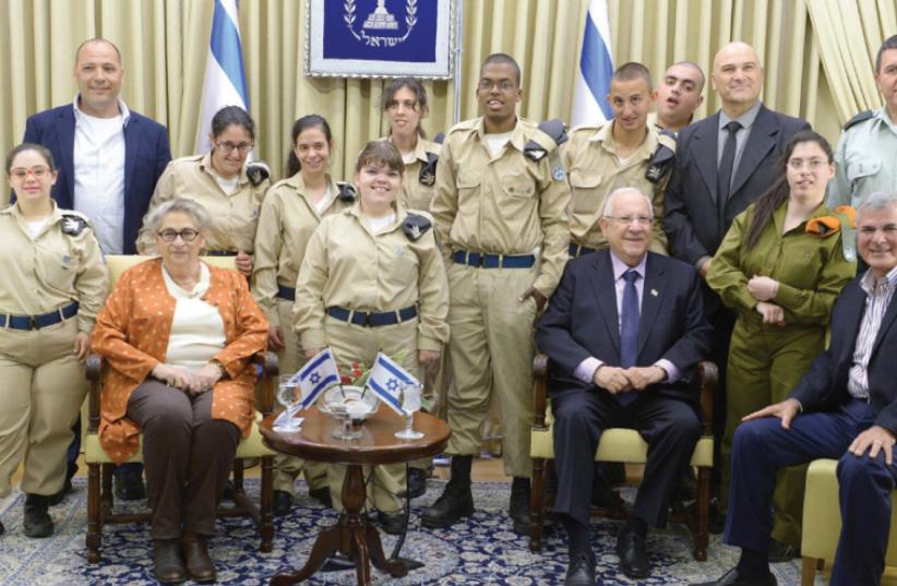 PRESIDENT REUVEN RIVLIN and his wife, Nechama, host a delegation of volunteer soldiers with special needs yesterday (photo credit: MARK NEYMAN / GPO)