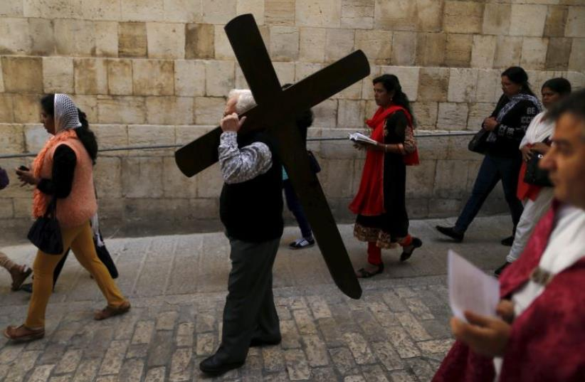 A worshipper carries a cross during a Good Friday procession through the Via Dolorosa in Jerusalem's Old City March 25, 2016 (photo credit: REPRODUCTION PHOTO: BENNY RON)