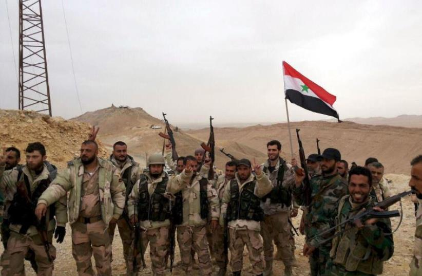 Forces loyal to Syria's President Bashar al-Assad flash victory signs and carry a Syrian national flag on the edge of the historic city of Palmyra in Homs Governorate, in this handout picture provided by SANA on March 26, 2016.  (photo credit: REUTERS)