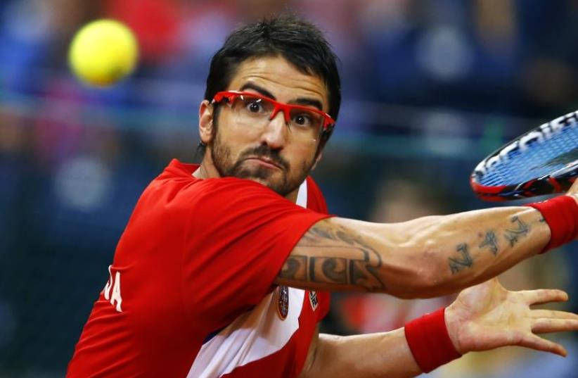 Serbia's Janko Tipsarevic returns the ball to Canada's Vasek Pospisil during their Davis Cup semi-final tennis match in Belgrade September 15, 2013. (photo credit: REUTERS)