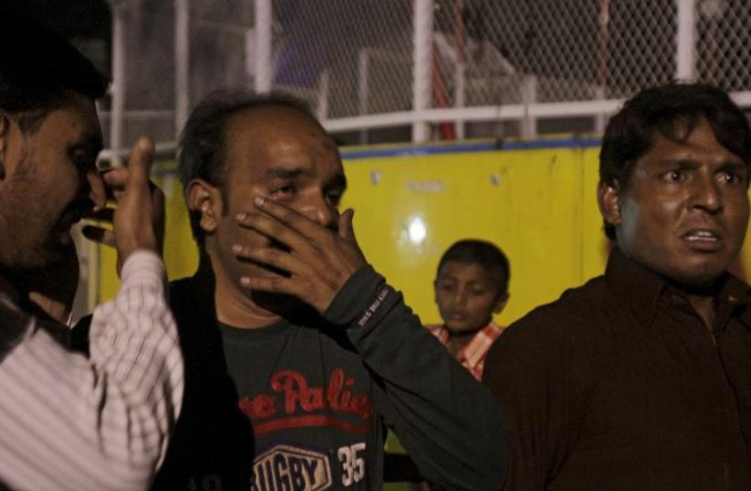 Men mourn the death of their relatives after a blast outside a public park in Lahore, Pakistan (photo credit: REUTERS)
