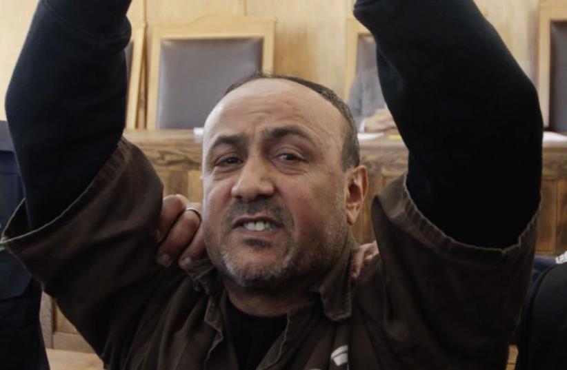 Jailed Fatah leader Marwan Barghouti gestures before a Jerusalem Magistrates' Court hearing in 2012. (photo credit: REUTERS)