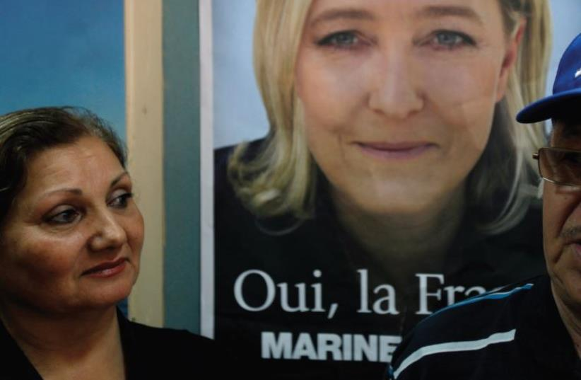 French nationals residing in Israel stand in front of a campaign poster of National Front presidential candidate Marine Le Pen, as they wait to vote in the French presidential election, at a polling station in Ashdod, April 22, 2012. (photo credit: REUTERS)