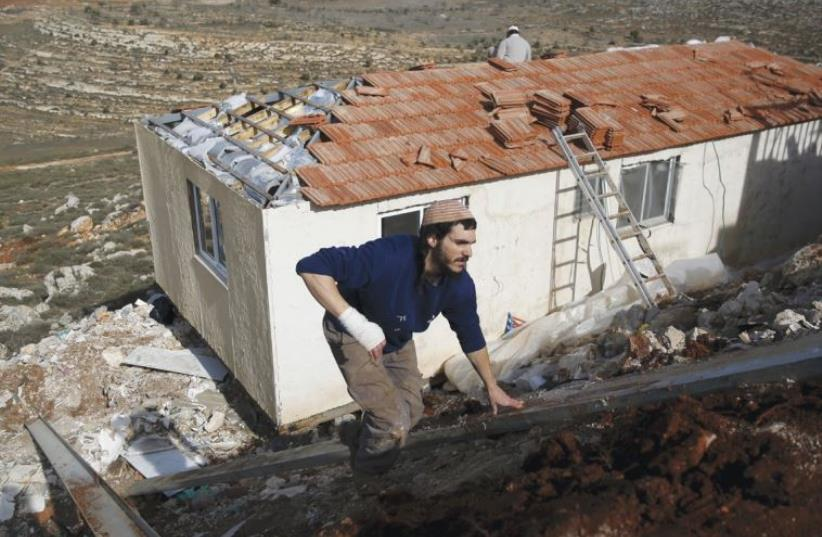 SETTLERS WORK on the construction of a house in the outpost of Achia in the Binyamin region (photo credit: REUTERS)