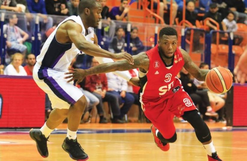 Hapoel Tel Aviv guard Nate Robinson (right) drives past Ironi Nahariya's Michael Umeh (left) (photo credit: ERAN LUF)