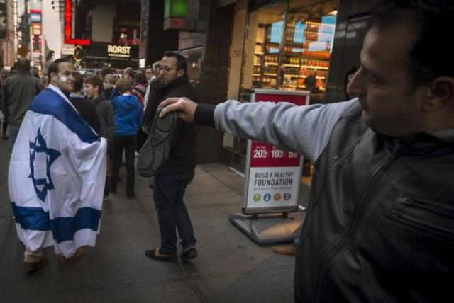 A man, draped in an Israeli flag, reacts while walking past a pro-Palestinian demonstrator who threatens to throw a shoe at him in New York (photo credit: REUTERS)