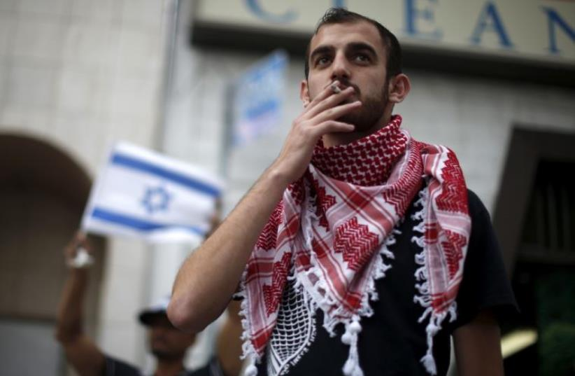 A Palestinian protester stands next to an Israeli counter-protest during a demonstration in Los Angeles (photo credit: REUTERS)