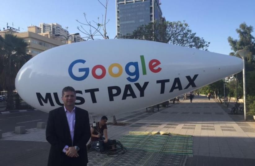 Likud MK Yoav Kisch stands next to protest blimp calling for Google to pay taxes (photo credit: Courtesy)