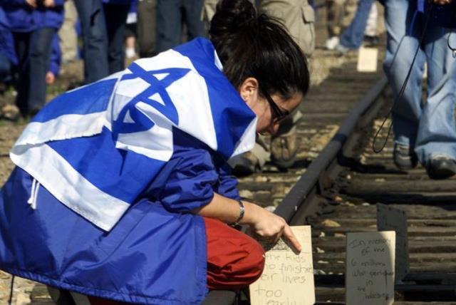 A Jewish girl places a wooden board on railway tracks to commemorate her relatives killed at the former Nazi death camp in Auschwitz-Birkenau (photo credit: REUTERS)