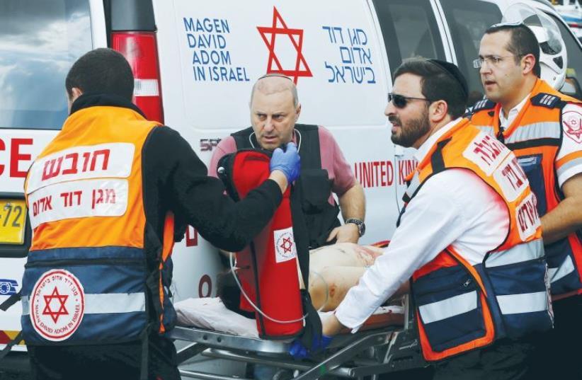 MDA MEDICS evacuate a Palestinian attacker in Jerusalem after a stabbing in October (photo credit: REUTERS)
