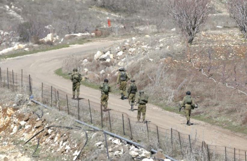 SOLDIERS PATROL a road near Majdal Shams in the Golan. (photo credit: REUTERS)