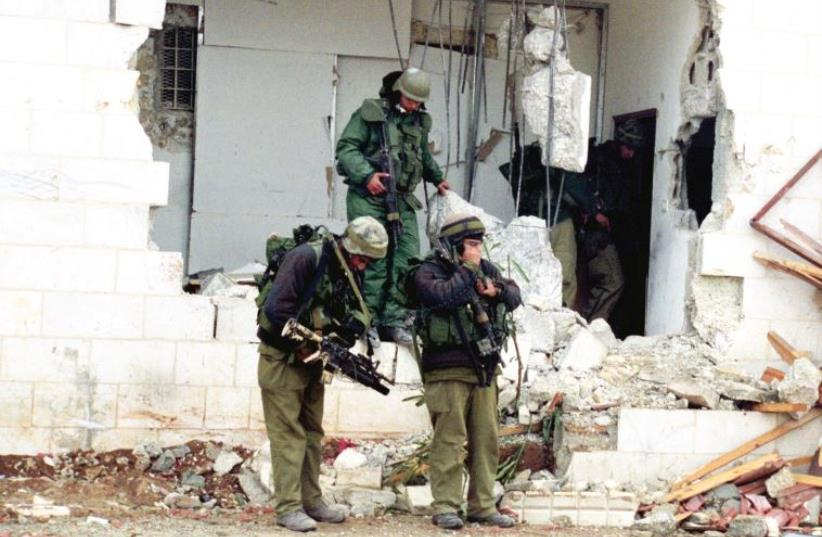 IDF soldiers maneuver in Ramallah during Operation Defensive Shield in 2002 (photo credit: IDF SPOKESMAN'S OFFICE)