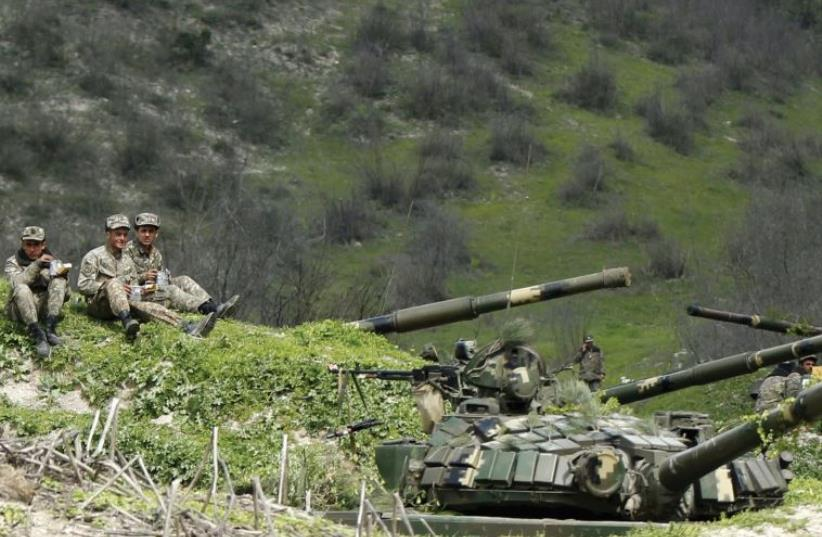 SERVICEMEN OF the army of Nagorno-Karabakh rest at their positions near the village of Mataghis, yesterday. (photo credit: REUTERS)