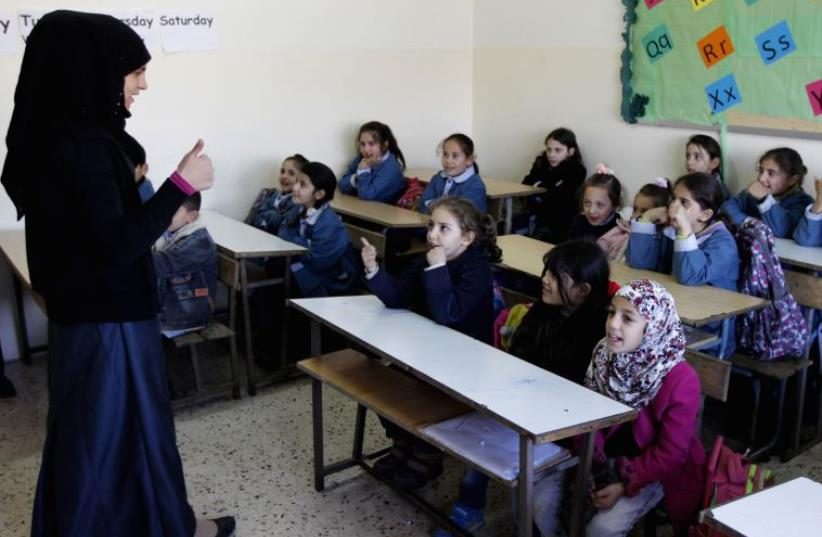 Syrian refugee children attend a lesson in their classroom, Lebanon (photo credit: REUTERS)