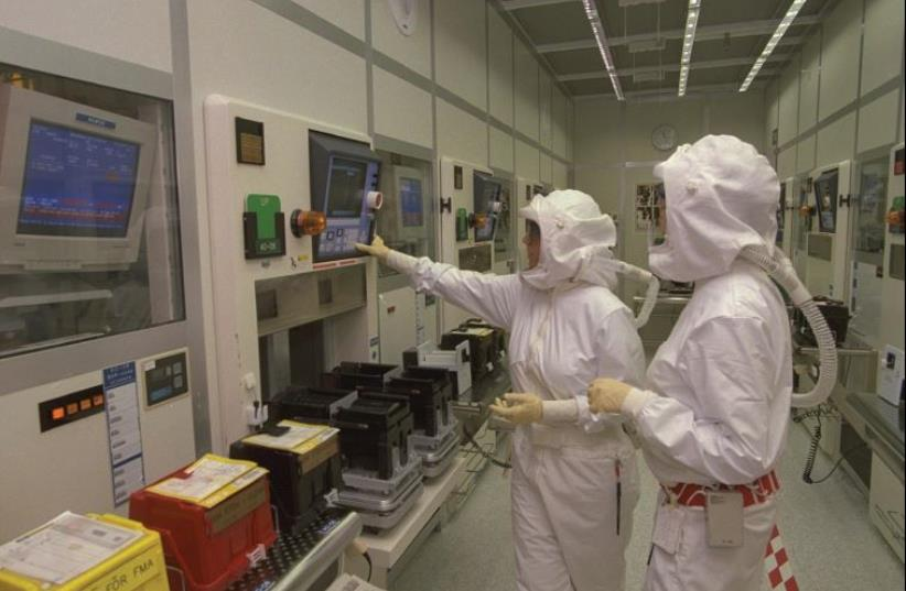 Technicians in sterile suits supervise the manufacture of computer chips in Intel's factory in Jerusalem (photo credit: AVI OHAYON - GPO)