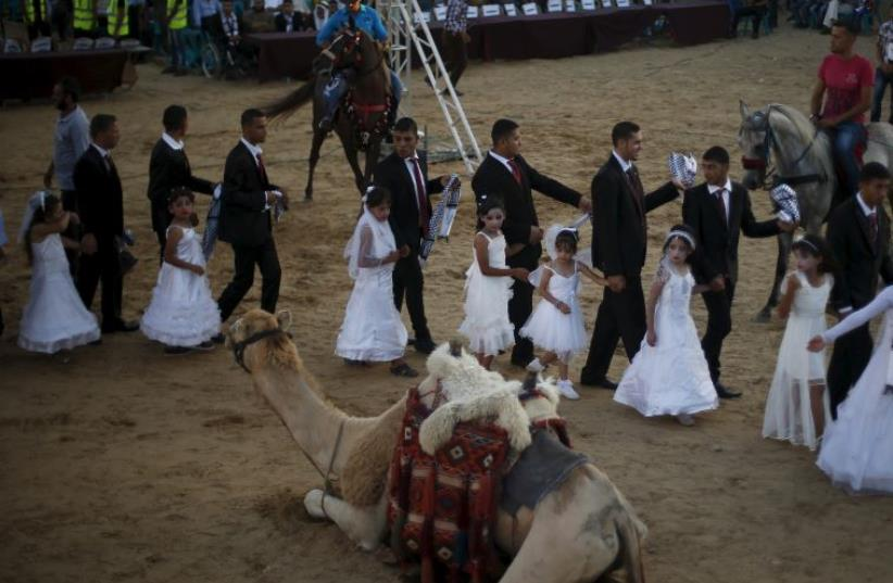 A camel is seen as Palestinian girls accompany grooms separate from the brides during a mass wedding for 150 couples, Gaza (photo credit: REUTERS)