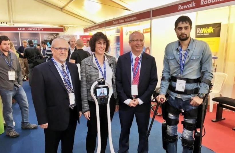 A representative for the company Rewalk (R) stands iwth Prof. Moshe Shoham, Dr. Sigal Berman and Professor Zvi Shiller at the Israeli Association of Robotics   (photo credit: LIAT MANDEL)