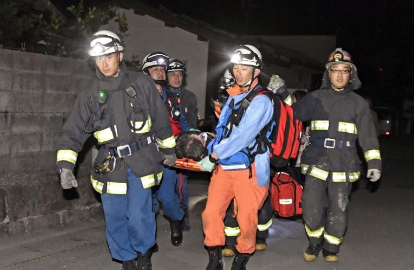 Rescue workers use a stretcher to carry a man who was rescued from a collapsed house after an earthquake in southern Japan April 15, 2016 (photo credit: REUTERS)