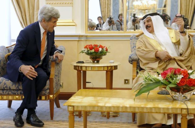 Bahrain's King Hamad bin Isa al Khalifa welcomes U.S. Secretary of State John Kerry at Gudaibiya Palace (photo credit: REUTERS)