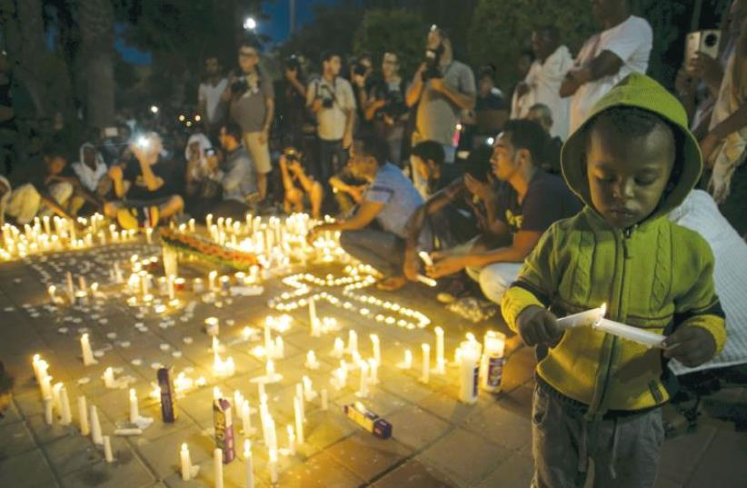 Israelis and fellow community members attend a memorial ceremony in Tel Aviv for Habtom Zarhum, an Eritrean migrant who was mistaken for a gunman at a shooting attack in Beersheba, in October 2015 (photo credit: REUTERS)
