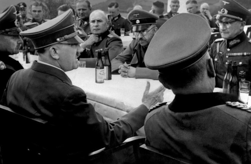 A picture dated 1939 shows German nazi Chancellor and dictator Adolf Hitler (4th L, no uniform) having a drink with high rank officers of his general staff including Heinrich Himmler (background, glasses and moustache) during a military campaign at the beginning of World War II. (photo credit: AFP PHOTO)