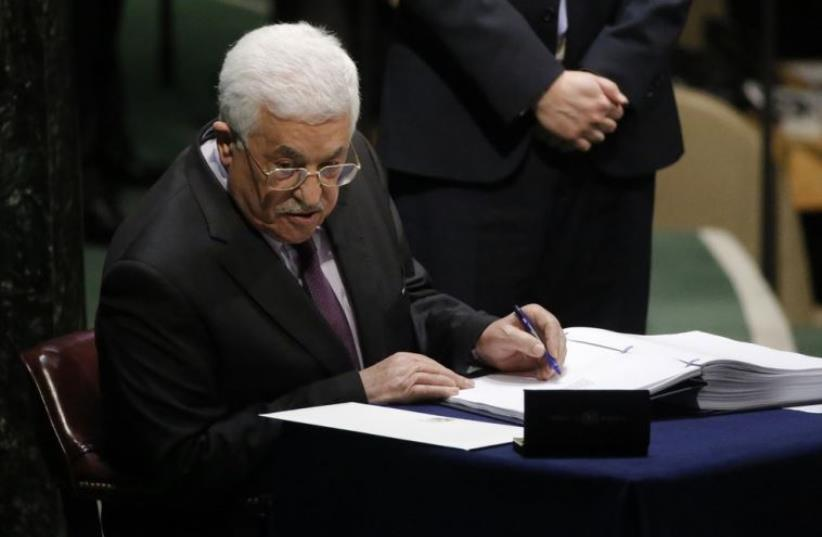 Palestinian Authority President Mahmoud Abbas signs the Paris Agreement on climate change at UN headquarters in New York (photo credit: REUTERS)