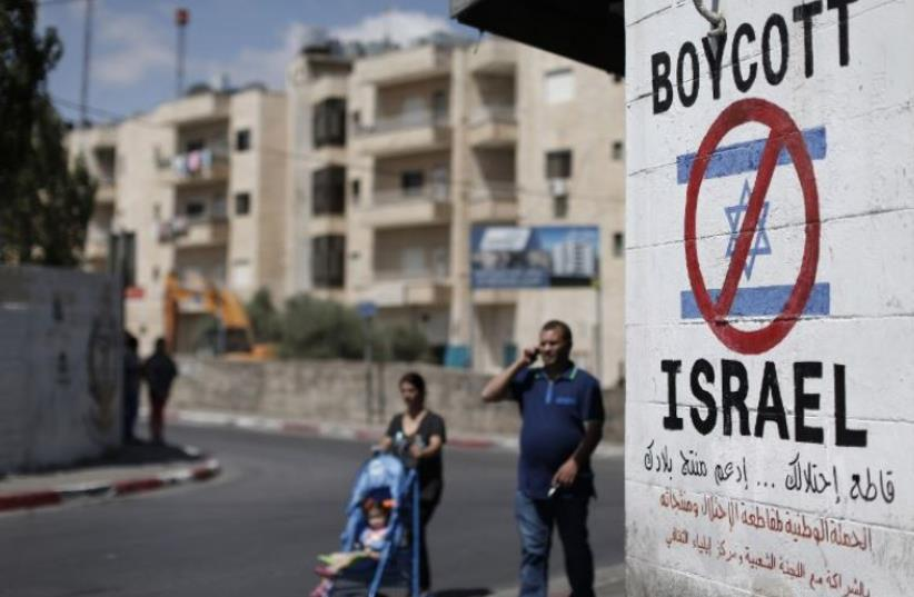 Palestinians walk past a sign calling for a boycott of Israel painted on a wall in Bethlehem (photo credit: AFP PHOTO)