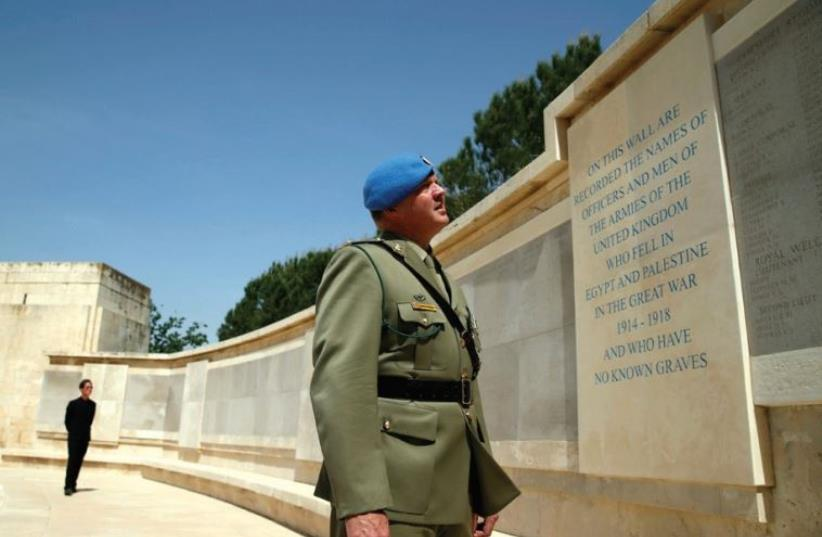 AN OFFICER reads the inscription on the Tomb of the Unknown Soldier memorial at the Mount Scopus Commonwealth War Graves Cemetery yesterday, ANZAC Day. (photo credit: REUTERS)