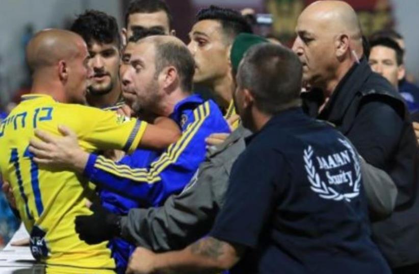 Maccabi Tel Aviv players and security staff engage in fisticuffs at Doha Stadium in Sakhnin (photo credit: SPORT1)