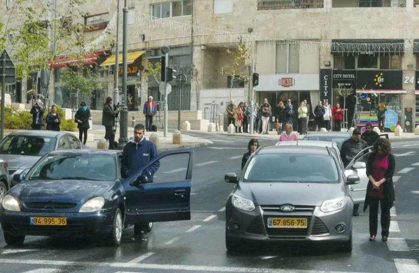 People stand outside their cars to observe a moment of silence on Holocaust Remembrance Day in Jerusalem (photo credit: MARC ISRAEL SELLEM)