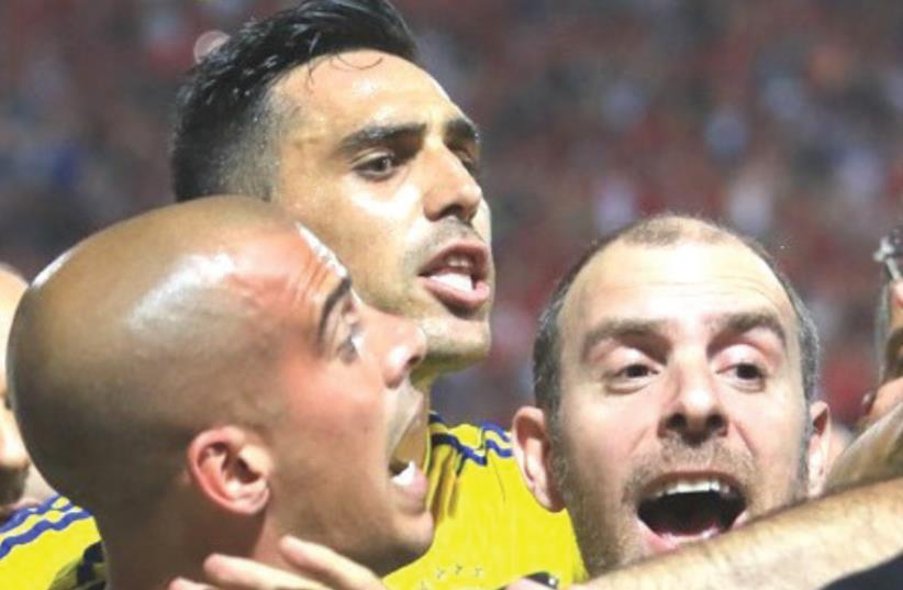 ISRAELI SOCCER made the headlines for all the wrong reasons once again on Monday night, with players from Maccabi Tel Aviv – including Tal Ben-Haim (left) and Eran Zahavi (center) – and Bnei Sakhnin players clashing following a 0-0 draw in Premier League action at Doha Stadium. (photo credit: ERAN LUF)