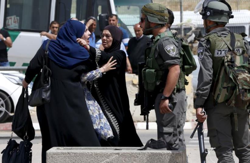 A Palestinian woman argues with border policeman near the scene of attempted stabbing attack at a checkpoint in Kalandiya (photo credit: REUTERS)