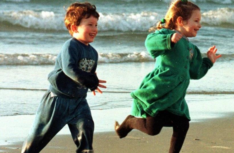 Children enjoy a sunny winter day on a Tel Aviv beach (photo credit: REUTERS)