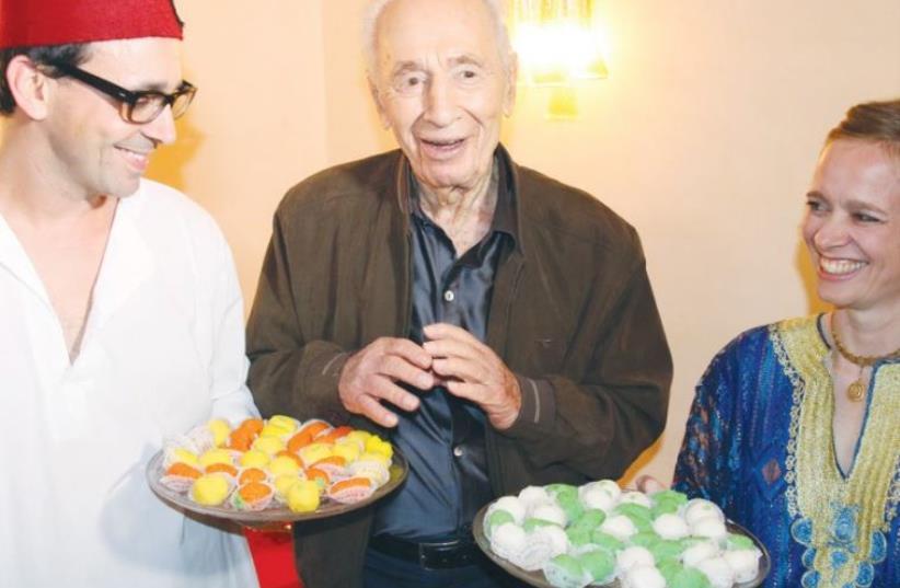 FORMER PRESIDENT Shimon Peres enjoys a post-Passover sweet at a Mimouna celebration in Tel Aviv yesterday. (photo credit: ELAD MALKA)